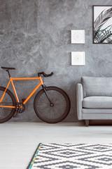 Orange bike next to sofa