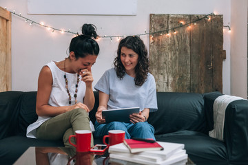 Two women friends use a tablet in apartment on sofa