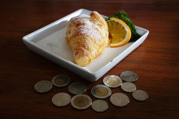 Dessert in a wooden tray with coin on a wooden table with sunlight in the morning.
