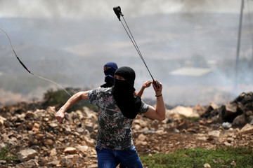 Palestinian protesters hurl stones towards Israeli troops during clashes following a protest against the near-by Jewish settlement of Qadomem, in the West Bank village of Kofr Qadom
