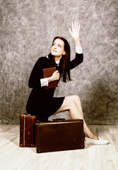 Retro woman with suitcase reading book waiting for a meeting, vintage style.