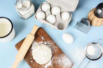 Making homemade cookies. Raw dough, rolling pin, sieve, eggs, flour and icing sugar on blue table
