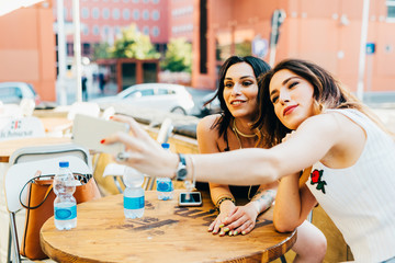 two young woman outdoor using smart phone taking selfie