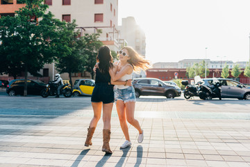 two young woman outdoor hugging laughing
