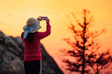 Girl traveler in hat take picture of suset