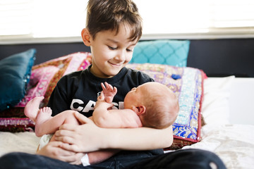 Boy holding small brother on bed at home