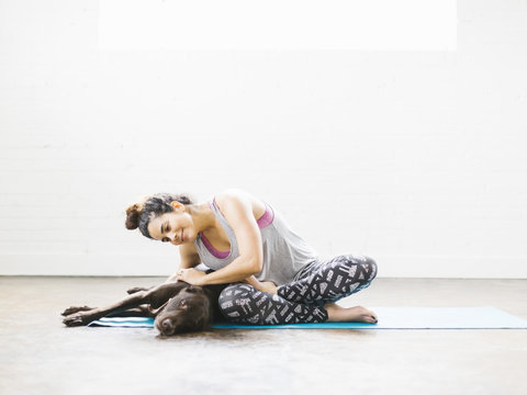 Woman practicing yoga with dog