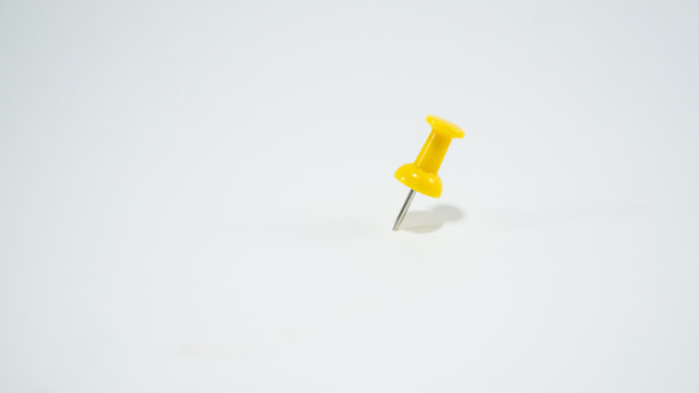 Yellow pins pinned on white paper.