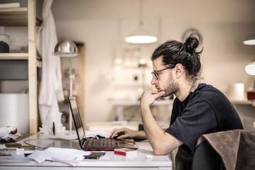 Geek guy working on his laptop