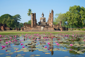 Ruins of ancient Buddhist temple Wat Chana Songkram on the shore of a lake with pink lilies. Sukhothai, Thailand