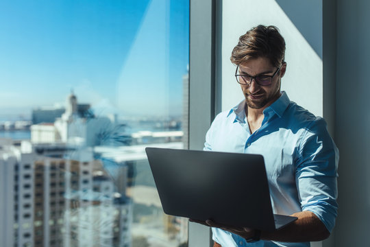 Business investor standing by a window holding a laptop.