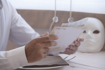 The hand of an old man looking at worn photographs, near a white mask.
