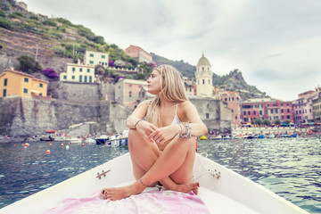 Beautiful blond girl sitting on the bow of boat