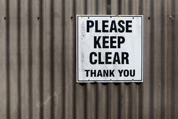 please keep clear sign on a corrugated iron garage door background