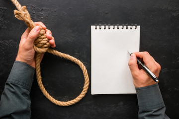 A man writes a suicide note and holds a rope loop