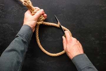 Man cuts with a knife suicide rope loop
