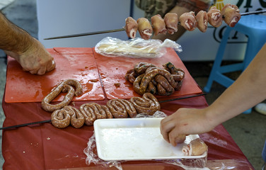 Prepare skewers with meat and sausage to be grilled during a festival