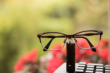 Image of congratulations on Teachers Day in modern style: big glasses, small book and keyboard of Personal Computer. Here is place for your great words on a nature background.