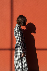 woman wearing checkered dress standing in front of a red wall