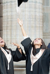 Happy and excited female graduates throwing hats in the air