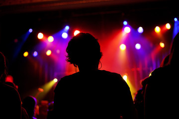Silhouette of girl with short hair and hoop earrings at a concert