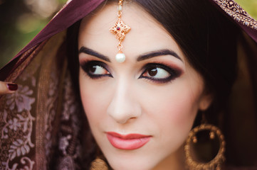 Portrait of beautiful indian girl . Young hindu woman model with tatoo mehndi and kundan jewelry.