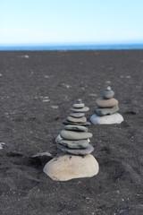 Piles de pierres sur la plage de sable noir en Islande