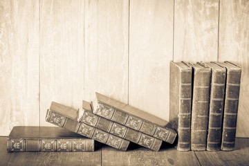 Vintage old books on wooden desk. Retro style sepia photo