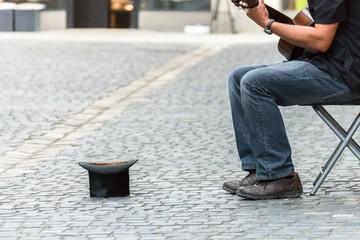 Zylinder Hut auf einem Kopfsteinpflaster und Straßenmusiker