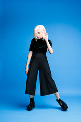 Attractive blonde girl in wide pants posing on blue background