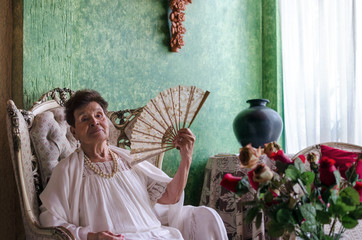Stylish Mexican old lady with a fan in her house full of antique
