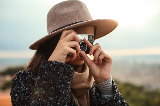 Woman taking a photo with her vintage camera outside.