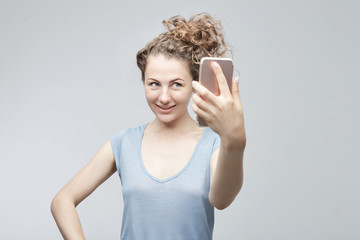 Young Caucasian cheerful woman with curly hair in bun in grey t-shirt making selfie using modern mobile phone, smiling at the camera, posing against white studio wall background. Technology concept.