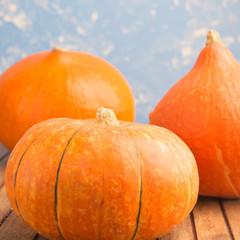 Three pumpkins on blue background