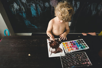 A child painting with watercolor for a homeschool activity