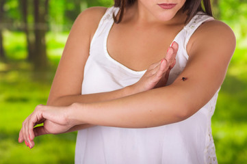 Close up of a young woman using her hand to kill a mosquito over her arm, in a blurred green background
