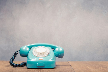 Retro old mint green telephone from 60s on table front textured concrete wall background. Vintage style filtered photo