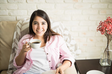 Woman drinking coffee in her apartment