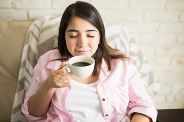 Young woman smelling freshly made coffee