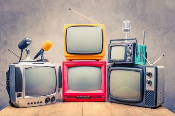Retro old TV set receivers and microphones on table front textured concrete wall background. Broadcasting concept. Vintage style filtered photo