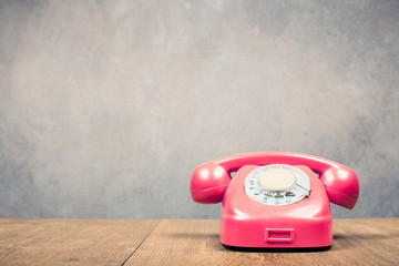 Retro old rotary telephone from 60s on table front textured concrete wall background. Vintage style filtered photo