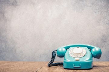 Retro old mint green telephone on wooden table front textured grunge concrete wall background. Vintage instagram style filtered photo