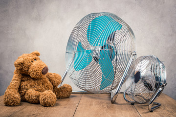 Retro Teddy Bear toy sitting near two office or home cooling fans on wooden table front concrete wall background. Vintage old instagram style filtered photo