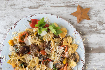 bowtie pasta with sausage and vegetables on plate top view closeup