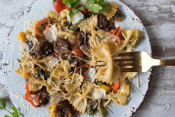 bowtie pasta with sausage and vegetables on plate top view with fork