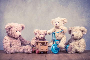 Retro Teddy Bear toys family: parents with kids on vehicles front concrete wall background. Parenthood concept. Vintage instagram old style filtered photo