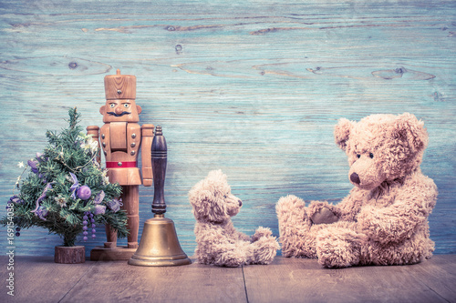 New Year tree, retro Teddy Bear toys, old bronze jingle bell and wooden nutcracker front textured wall background. Holiday greeting card concept. Vintage instagram style filtered photo
