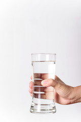 The hands of a beautiful woman holding a glass of water on a white background.