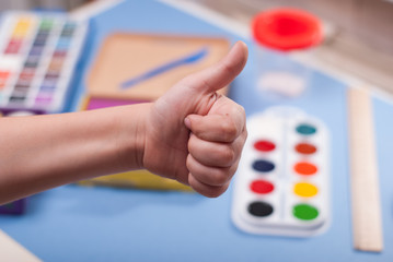 Children's hand showing thumb up as a positive sign., student approves