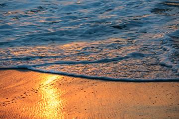 Sea foam at orange wet sand